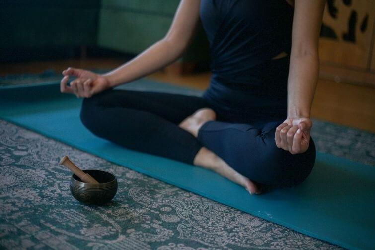 Meditation mit Klangschalen zu Hause Tipps Frau im Schneidersitz meditiert, vor ihr liegt eine Klangschale