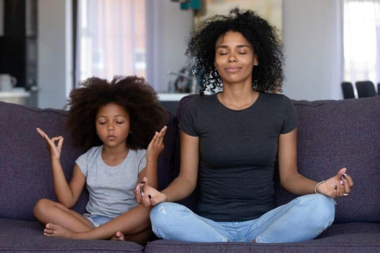 Achtsamkeitsübungen für Kinder Mutter meditiert mit ihrem Kind auf dem Sofa