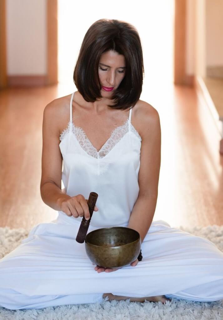 Klangschalenmeditation wird von einer Frau durchgeführt